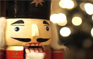 Close up of a nutcracker with blurred holiday lights in the background