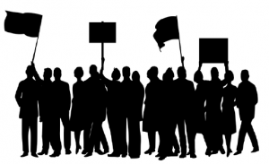 Group of people--silhouettes--holding up signs and flags