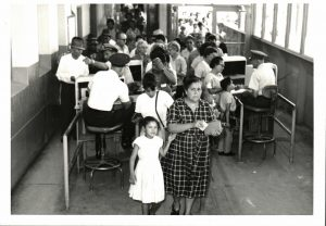 Black and white photograph; A women looks at the camera and so does a young girl to her right. There is a line of people behinf them.