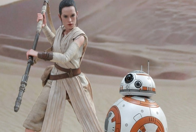 Rey stands in a desert looking down at a white and orange robot.