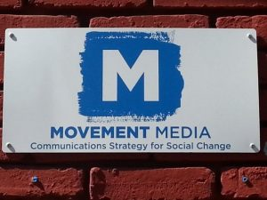 Sign that reads M Movement Media Communications Strategy for Social Change
