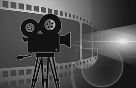 A clipart image of a black movie projector with film behind it.