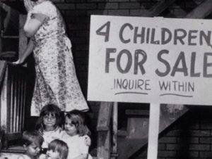 "Black and white photograph that shows for children sitting on steps and a woman satnding behind them. A sign the righht reads ""4 Children for Sale Inquire Within"""