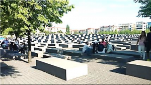 Visitors resting on the concrete slabs of the Memorial to the Murdered Jews of Europe. Photo by Amber Kalb.