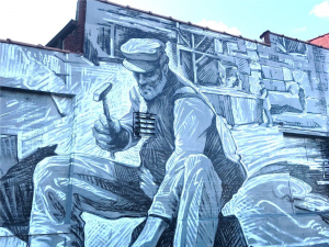 A man chiseling; mural in Eckington, Washington, D.C. Photo by Briana Pocratsky.