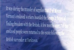 """A sign that reads """"It was during the transfer of supplies that 17 of Mount Vernons enslaved workers boarded the Savage in hopes of finding freedom with the British. A few months later, 7 of the enslaved people were returned to the estate follwoing the British surrender at Yorktown."""